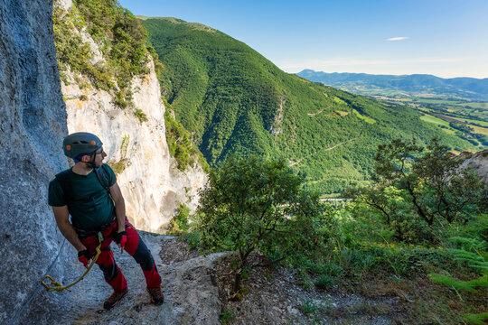 Male rock climber taking break to admire surrounding landscape of Apennine Mountains