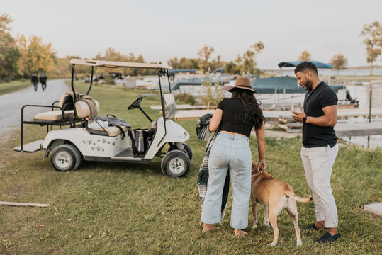 Couple with dog standing by golf cart outdoors