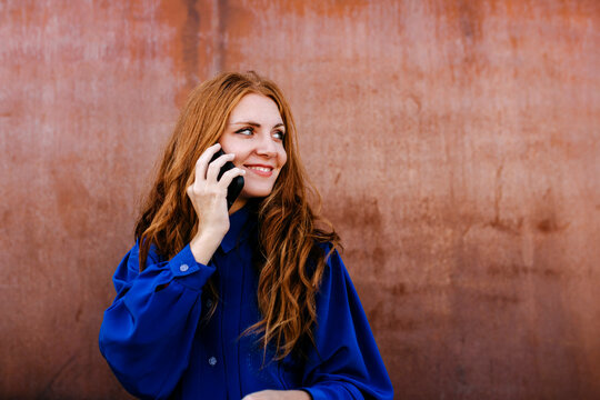 Smiling young woman talking on smart phone against wall