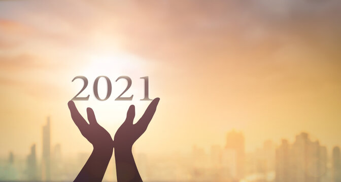 New year 2021 concept: Silhouette hands show 2021 against blurred city sunrise background