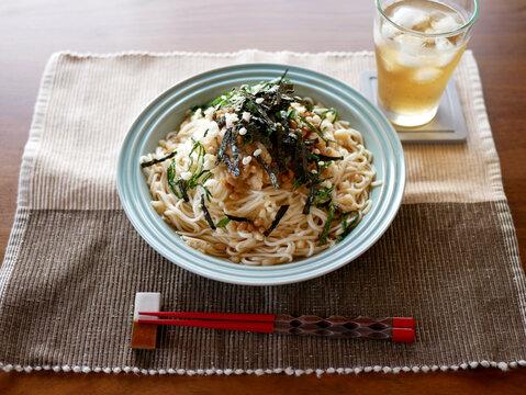 テーブルに置かれた、夏にぴったりの冷たいおろし納豆うどんと麦茶