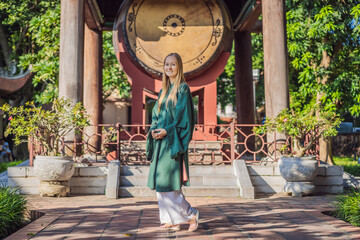 Woman tourist in national vietnamese dress in Temple of Literature in Hanoi in Southeast Asia, Vietnam. Vietnam reopens after coronavirus quarantine COVID 19