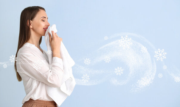 Young woman smelling clean laundry on color background