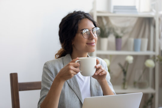 Peaceful moment. Tranquil young woman freelancer drinking hot beverage at office desk satisfied with good work results. Millennial female designer enjoying self realization in creative profession