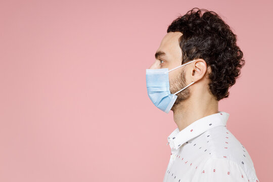 Side view of young bearded man 20s in basic white shirt sterile face mask to safe from coronavirus virus covid-19 during pandemic quarantine isolated on pastel pink color background studio portrait.