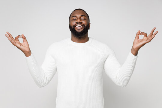 Smiling young african american man 20s wearing casual basic sweater standing hold hands in yoga gesture relaxing meditating trying to calm down isolated on white color wall background studio portrait.