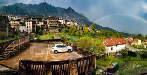 Panorama of the village of Poffabro, one of the most beautiful villages in Italy, with the rainbow on background after the storm, in the Friulian Dolomites natural park