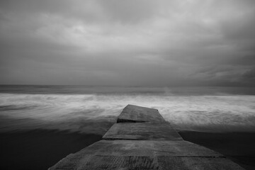 old stone pier and a stormy seascape