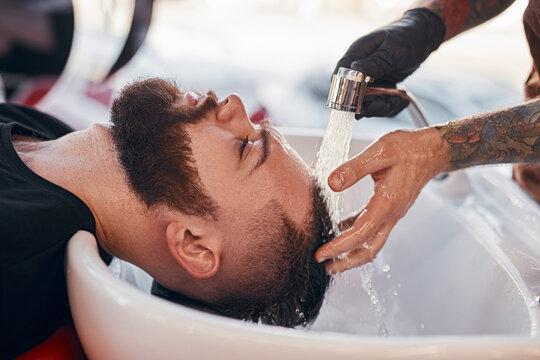 Crop barber washing hair of hipster