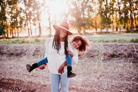 portrait of hispanic mother and afro kid girl playing outdoors at sunset during golden hour. Autumn season. Family concept