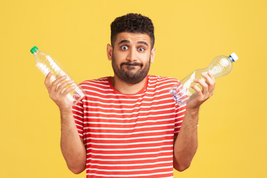 Confused puzzled man with beard in striped red t-shirt holding two plastic bottles and shrugging shoulders, not aware of plastic recycling. Indoor studio shot isolated on yellow background