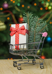 Grocery shopping cart with gift box and pine inside on cgristmas tree background
