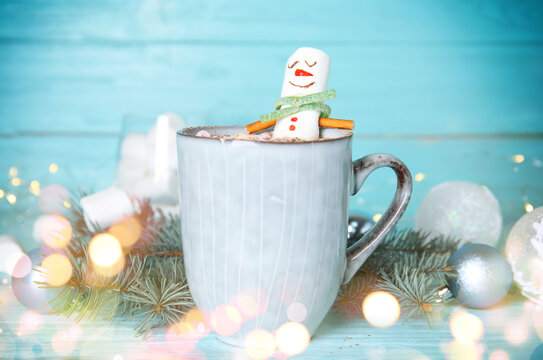 Funny marshmallow snowman in cup of hot drink on light blue wooden table. Bokeh effect