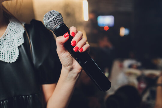 Microphone and unrecognizable female singer close up. Cropped image of female singer in pink dress , singing into a microphone, holding mic with two hands. Copyspace.