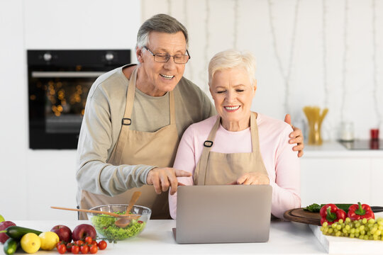 Older Couple Cooking Using Laptop In Modern Kitchen At Home