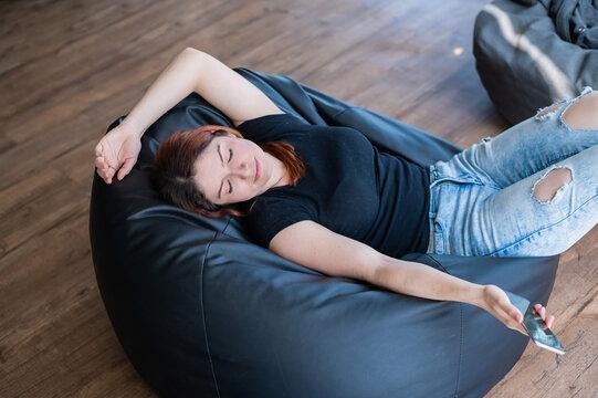 Caucasian young woman sleeping on bean bag