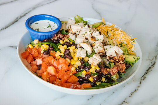 Southwest salad with tomatoes beans corn chiken cheese and avacados with a side of ranch
