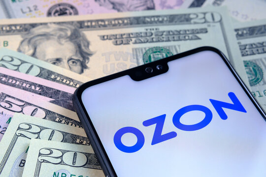 Stafford / United Kingdom - November 15 2020: Ozon E-commerce company logo seen on the screen of smartphone, placed on dollar bills. Concept for initial public offering.