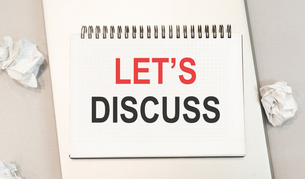 The word let's discuss is written in a notebook that sits on a gray desktop along with a laptop.