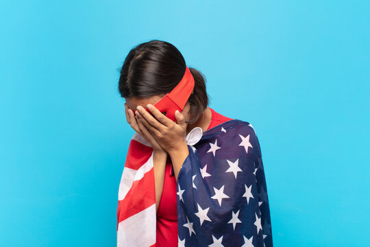 young latin woman covering eyes with hands with a sad, frustrated look of despair, crying, side view