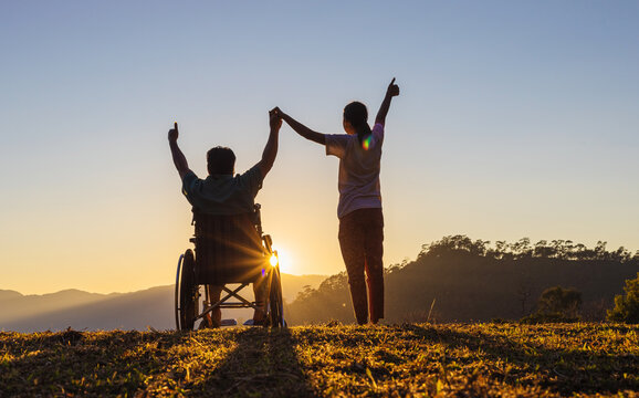 Disabled handicapped young man in wheelchair raised hands with his care helper in sunset.Silhouette