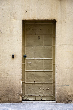 An old but strong steel door in a dirty cream rendered buidling wall in an alley way in the city