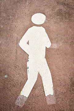 an old, weathered and fading pedestrian symbol with parts of the symbol being broken away, vertical