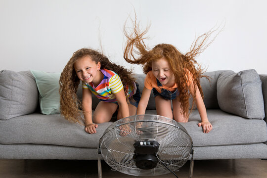 Two funny young girls on couch facing a fan