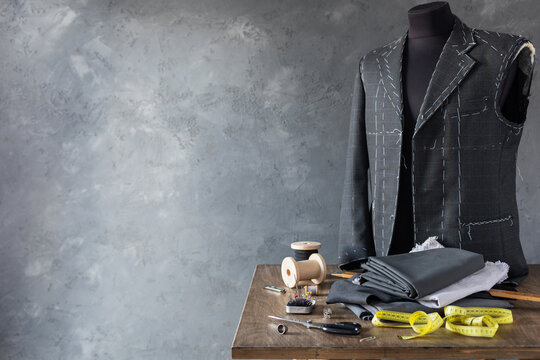 suit jacket on male tailor mannequin and sewing tools