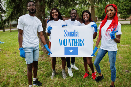Group of happy african volunteers hold blank with Somalia flag in park. Africa countries volunteering, charity, people and ecology concept.