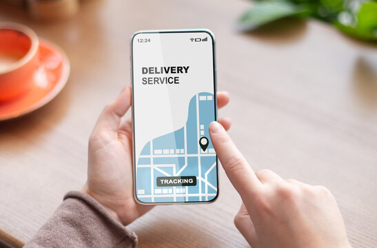 Woman using smartphone with opened delivery service tracking app, checking order status