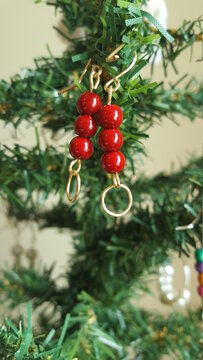 Red, Tripple beaded gold wire earrings displayed in front of a Christmas Tree's branches. The branches are blurred allowing for the display of the vibrant, Red, and gold of the hanging earrings.