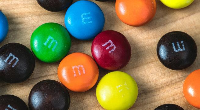 Chocolates M&Ms em close up sobre objeto de madeira.