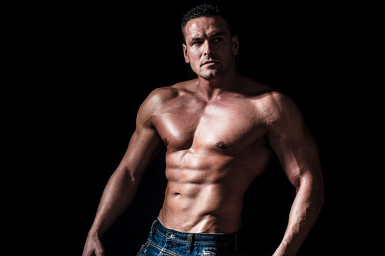 Torso with six pack and ab muscle. Abs and biceps. Strong brutal guy. Sexy torso. Handsome big muscles man posing at studio. Muscular sexy man. Handsome sexual strong man with muscular body