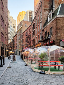 New York City, USA - 2020: Outdoor dining tables in front of the historic buildings on Stone Street during the coronavirus pandemic in downtown Manhattan