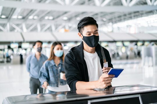 Asian male wearing face mask traveler giving boarding pass and passport to customer check in officer at service counter airport.Man wearing face mask when traveling to prevent coronavirus pandemic.