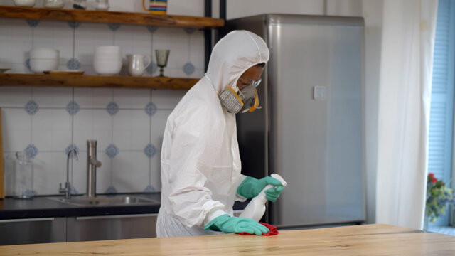 Disinfector in protective suit and mask spraying detergent and wiping table in house kitchen