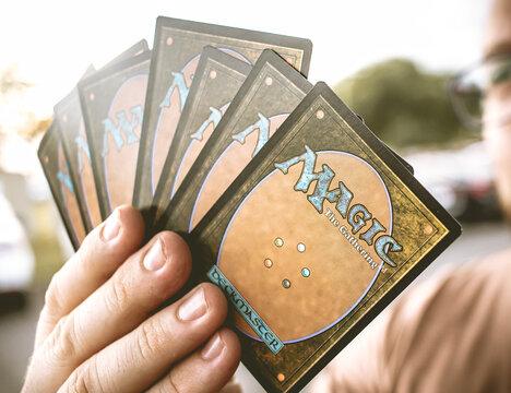 Magic: The Gathering. Homem segurando cartas do jogo de estratégia Magic: The Gathering.