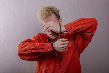 Fototapeta portrait of a teenager in handcuffs, covering his face with his hands on a gray background, medium plan. Perhaps he is ashamed of what he has done. juvenile delinquent, criminal liability of minors. M obraz