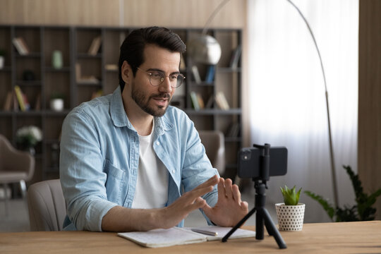 Millennial Caucasian male coach or speaker record live broadcast on smartphone camera at home. Young man tutor talk speak on video call or webcam digital conference on cellphone. Training concept.