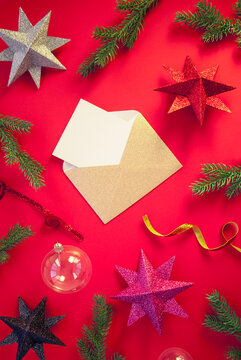 Spruce branches, decorative balls with stars on red background with envelope and paper card note. Christmas composition. Happy New Year. Space for text. Flat lay, top view