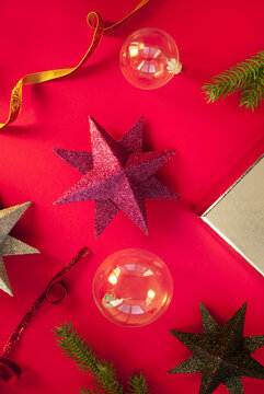 Spruce branches, decorative balls with stars on red background. Christmas composition. Winter holiday theme. Flat lay, top view