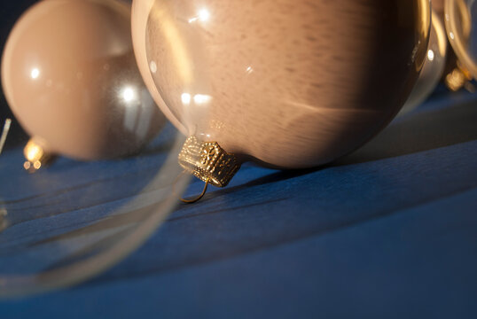 Christmas bauble decoration on blue background with long shadows. Christmas composition. Winter holiday theme