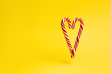 Christmas candy cane in the shape of a heart on a yellow background.