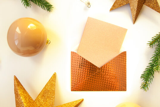 Envelope with paper card note, gold stars, spruce branches and decorative balls on white background. Christmas composition. Happy New Year. Space for text. Flat lay, top view