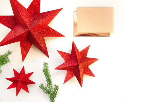 Red stars, spruce branches with envelope and paper card note on white background. Christmas composition. Happy New Year. Space for text. Minimal style. Flat lay, top view