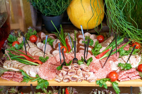 buffet at the reception. Glasses of wine and champagne. Assortment of canapes on a wooden board. Banquet service. food, snacks with cheese, jamon, prosciutto and fruit