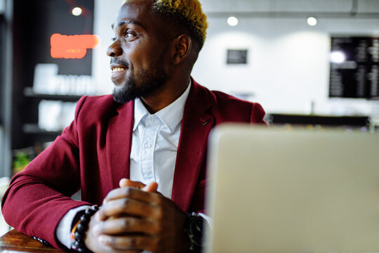 african american person sitting at office typing message note on phone near laptop