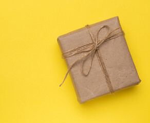 Obraz square box with a gift wrapped in brown paper and tied with a brown ro - fototapety do salonu