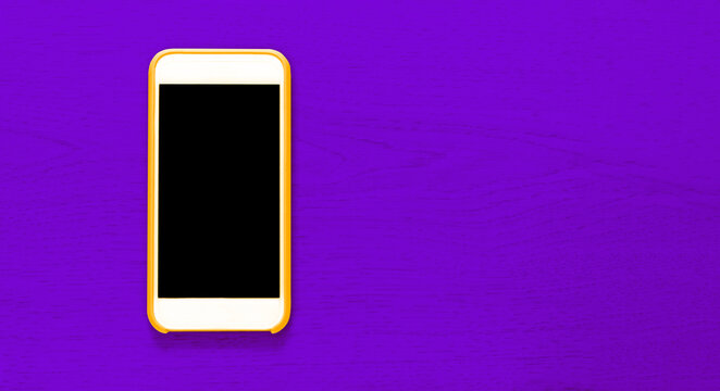Top view of yellow cell phone with isolated black screen that contrasts with purple background with wood texture and ample copytext space